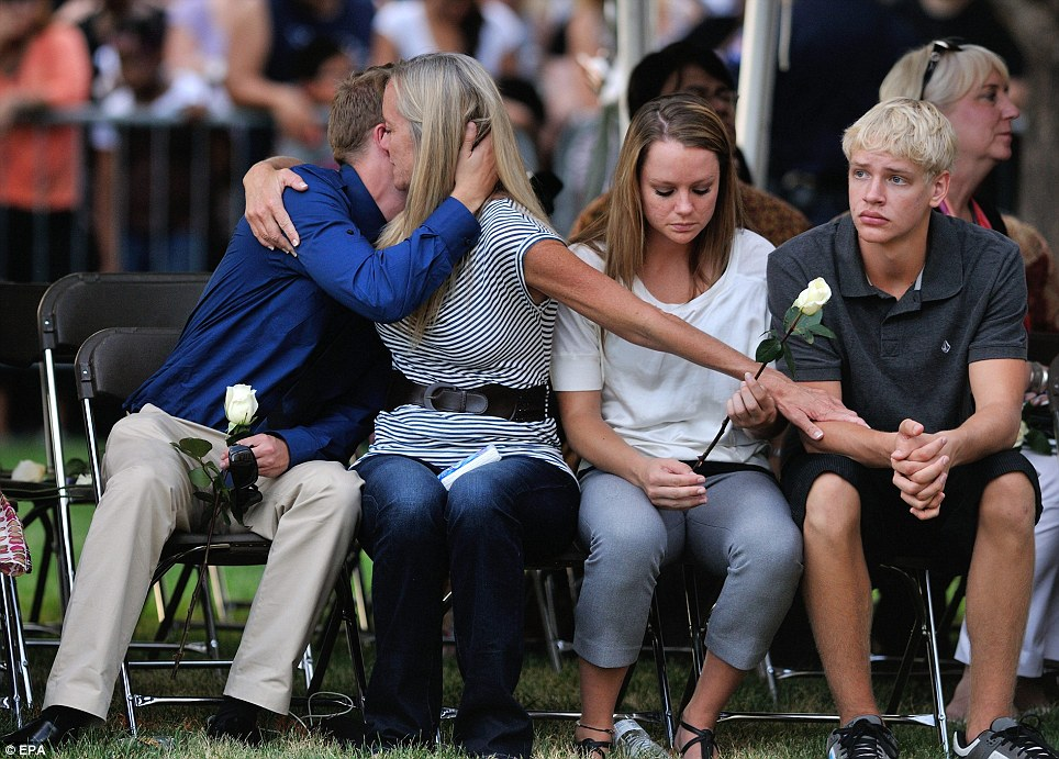 A family console one another during a memorial service at the Aurora Municipal Centre in Aurora, Colorado, following an attack at the Century 16 Theatre shooting