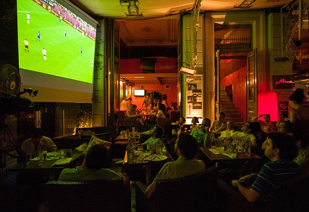Footballers in Greece watch this year's Euro 2012 football tournament on a TV set receiving the same footage beamed around the world