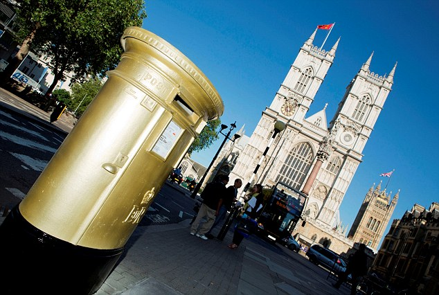The first of the Royal Mail post boxes painted gold to mark the London 2012 Games, outside Westminster Abbey