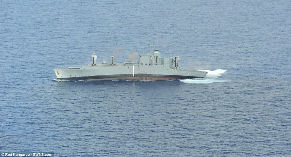Hole lot of trouble: Kilauea tilts to one side as water rushes though the hull. Two other inactive vessels will also be sent to a watery grave by torpedoes, bombs and other ordnance during the Rim of the Pacific naval exercises