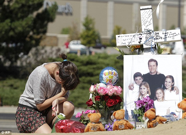 Emotion: Ashley Deuell, 18, kneels next to a cross and family photo of Cowden, a friend of her family