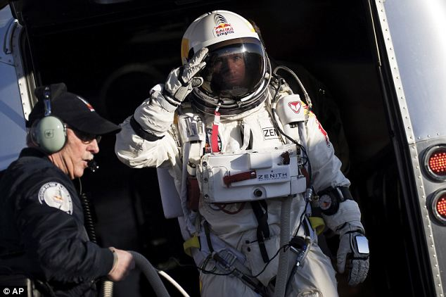 Fearless: Mr Baumgartner salutes as he prepares to board the capsule carried by a balloon that will take him up 18 miles above the surface of the Earth