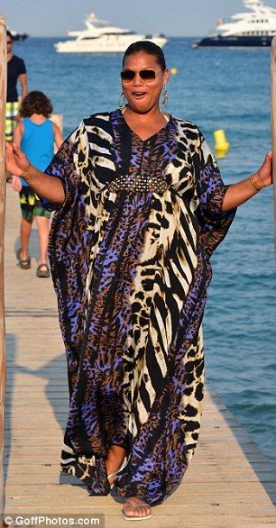 Happy holiday: Despite her garish choice of outfit, Queen Latifah was all smiles as she arrived at Club 55 in St Tropez yesterday