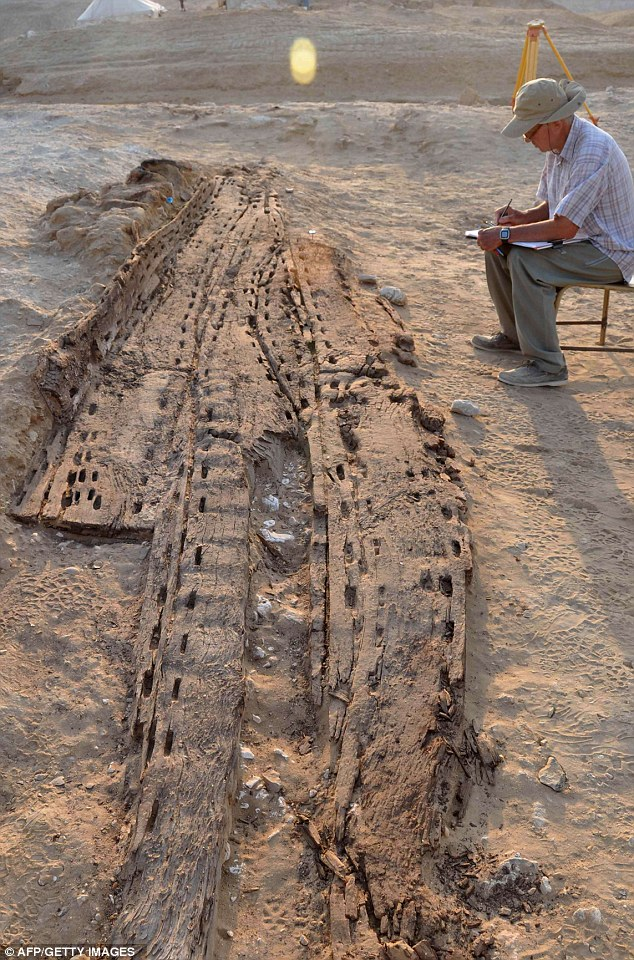 Stunning: An archaeologist is seen working on the skeleton of the newly discovered wooden boat. The pharaohs believed that solar boats, buried close to them at death, would transport them in the afterlife