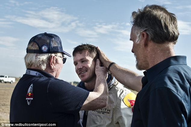 Well done: Mr Thompson and Mr Kittinger, the world record holder, welcome Mr Baumgartner back to Earth