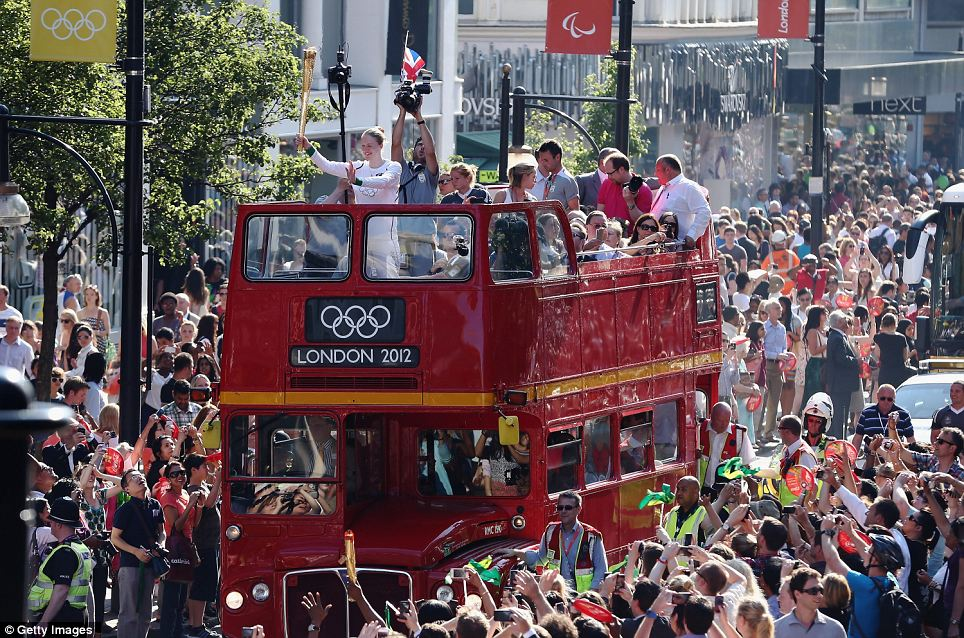 Open flame: The Olympic Torch is carried on top of an open top bus down Oxford Street as it nears the end of its 70 day journey