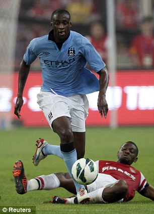 Getting there first: Manchester City's Yaya Toure fights for the ball against Arsenal's Abou Diaby