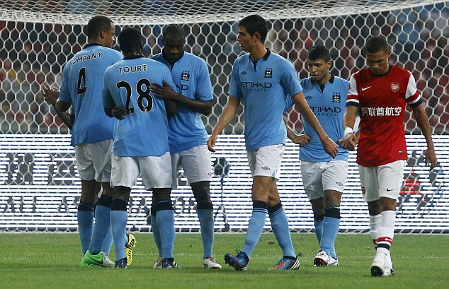 Winning in the rain: Manchester City's Yaya Toure celebrates with teammates after scoring against Arsenal