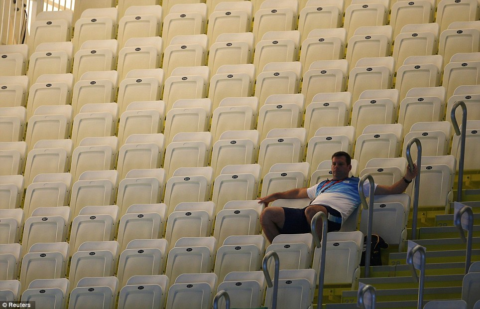 All by myself: A spectator sits among empty seats as he waits for the start of the final session on the first day of the swimming competition at the Aquatics Centre