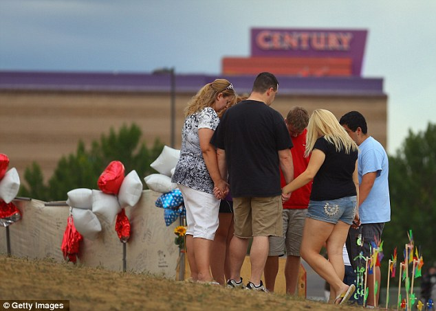 Visitors pray together around a cross erected at a memorial setup across the street from the Century 16 movie theater on July 28, 2012 in Aurora, Colorado
