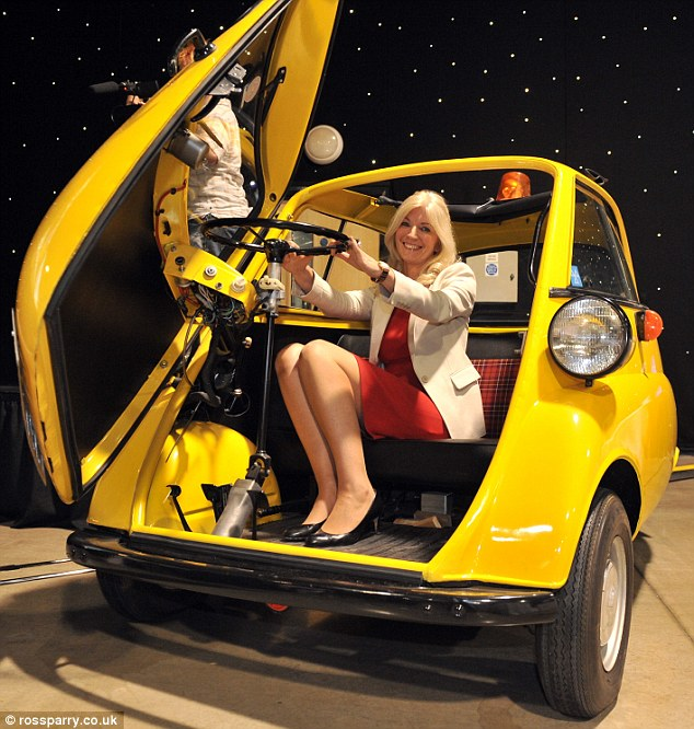 Delighted: Angela Swift is all smiles after buying Sir Jimmy Savile's BMW Isetta for £22,000 at an auction in his hometown of Leeds