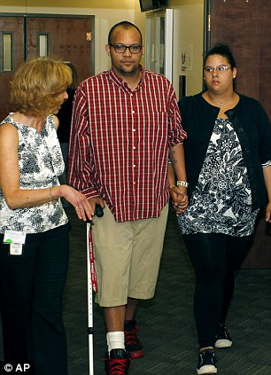A victims advocate, left, escorts victims as they arrives for an arraignment for suspected theater shooter James Holmes in district court in Centennial, Colo., on Monday, July 30, 2012.