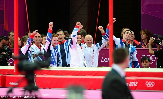 Britain's team members react at the end of the men's team final of the artistic gymnastics event