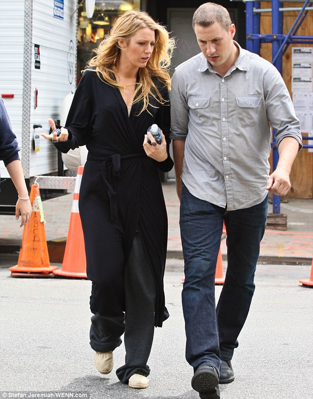 Down at heel: Blake Lively chats to a male friend outside her trailer while sporting a distinctly low fashion ensemble of a black dressing gown and grey tracksuit bottoms in New York earlier today