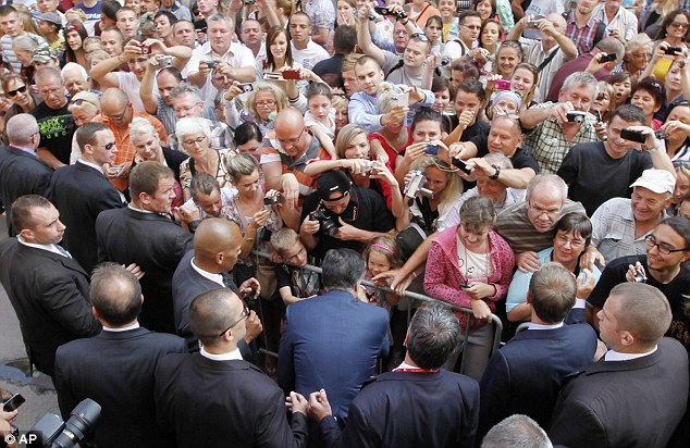 Welcomed: Mitt Romney was greeted by hundreds of eager people who leaned in to get a glimpse of the Republican candidate in Poland