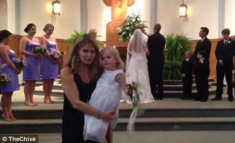 Graceful exit: The worn-out flower girl was carried away in the arms of a woman who appeared to be her mother