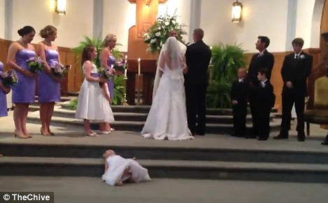 Quiet time: Little Claire had just spread out below the altar when her antics were spotted by the couple and the priest, who briefly paused the ceremony