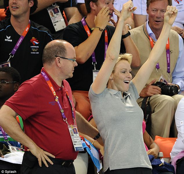 Crown Princess Charlene and Prince Albert of Monaco celebrate a South African victory in the men's 200 meter Butterfly event