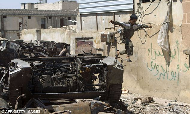 War games: A Syrian boy jumps off a destroyed army armoured vehicle in the northern town of Atareb, near Aleppo