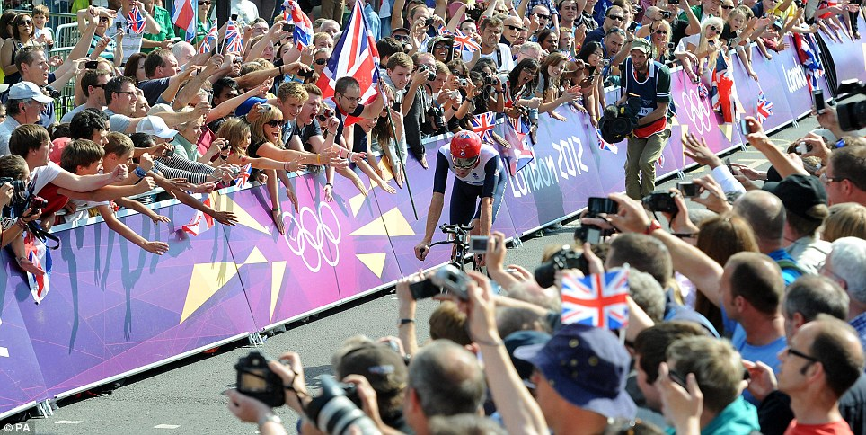 Roaring fans create a corridor of support for Wiggins as he approaches the finish line at Hampton Court