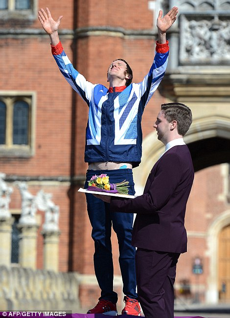 Britain's Bradley Wiggins celebrates on the podium after winning the gold