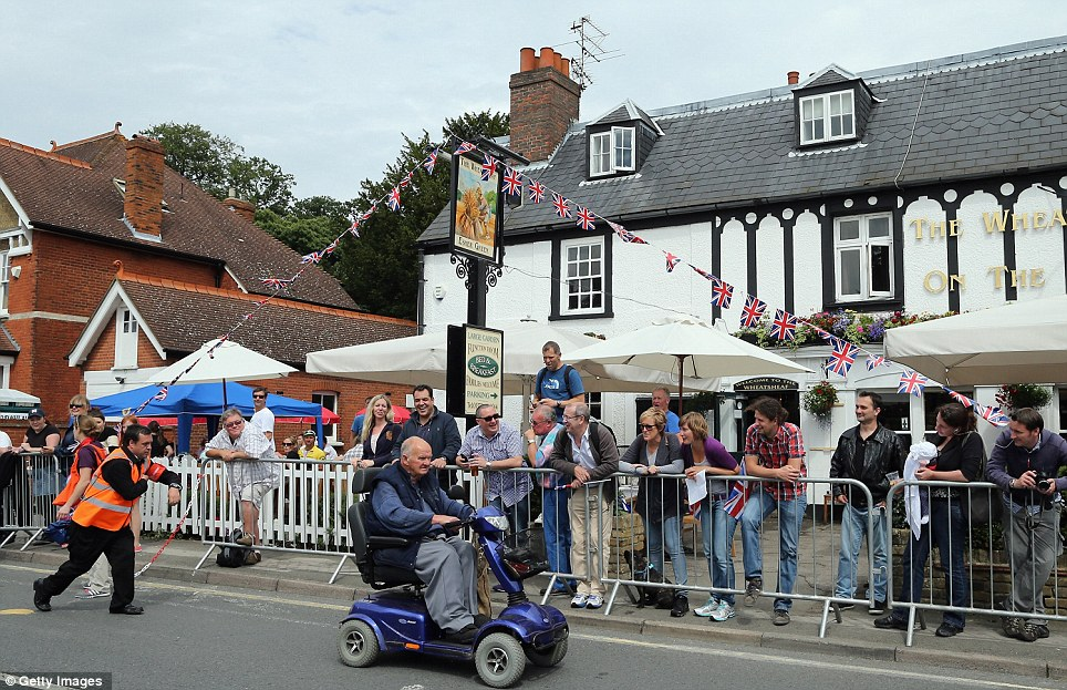 An official chases after a man on a mobility scooter as he attempts to drive down the route of the Olympic time trial in Esher