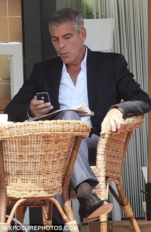 Passing the time: The Ocean's Eleven star was seen whistling as he checked his iPhone in between takes
