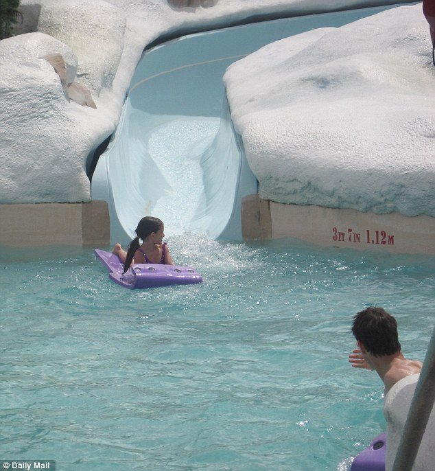 Hold on tight: Suri whizzes down the the water slide on a purple float as Tom looks on