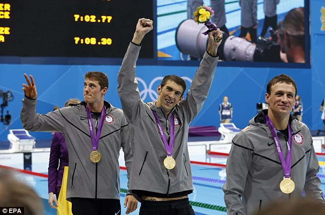 Winner: Michael Phelps, pictured centre, celebrates swimming into the record books as the most decorated Olympian after winning gold in the relay with teammates Ryan Lochte, right, and Conor Dwyer, left