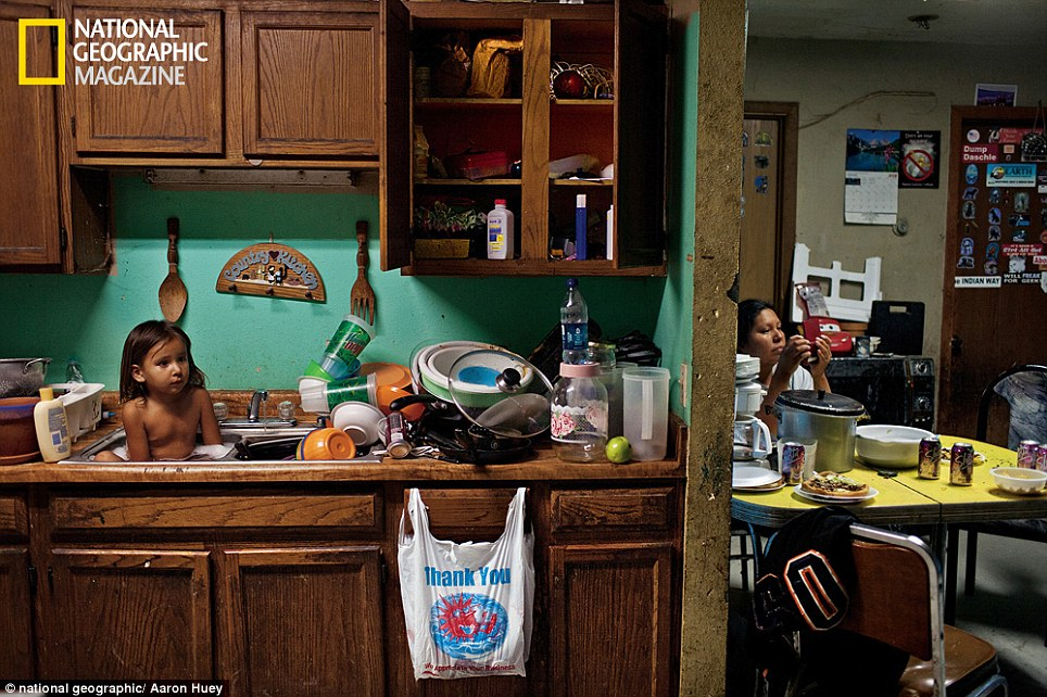 Three-year-old C. J. Shot bathes among dishes. The Oglala concept of tiospaye 'the unity of the extended family' means that homes are often overcrowded, especially with the severe housing shortage on the reservation