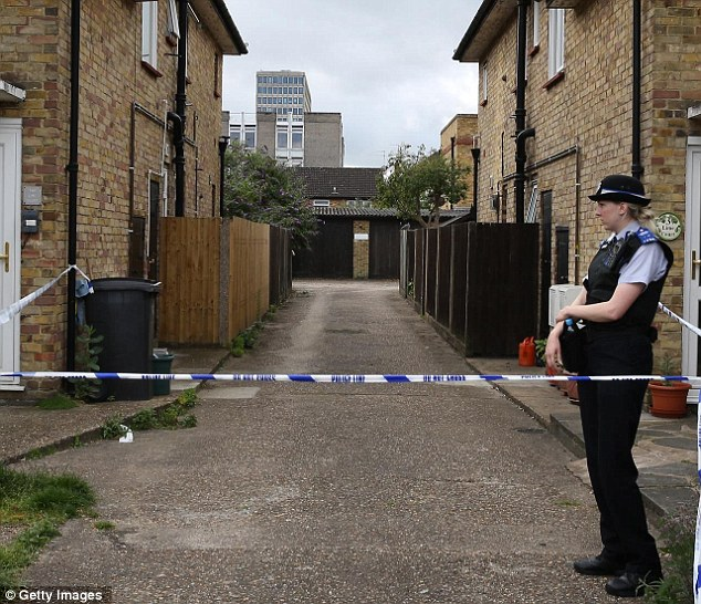 A police officer stands outside lock-up garages in New Malden as police search for clues surrounding the discovery of Ms Waugh's body
