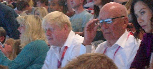 Entertaining: Johnson and Murdoch watch the swimming in the Olympic Park last night