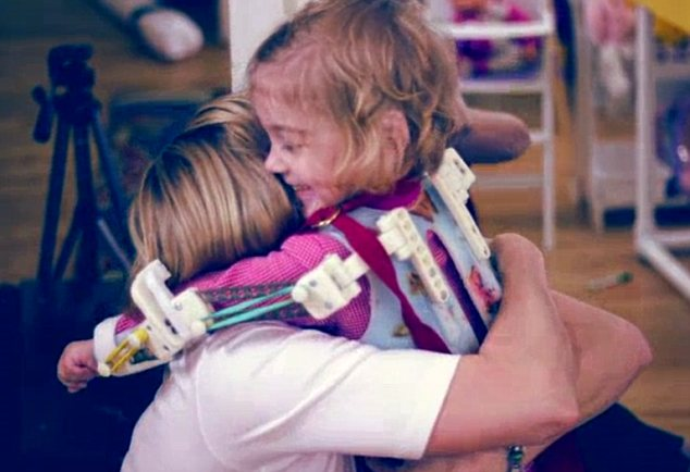 Mother and daughter: Emma can hug her mother Megan Lavelle with help of her 'magic arms'