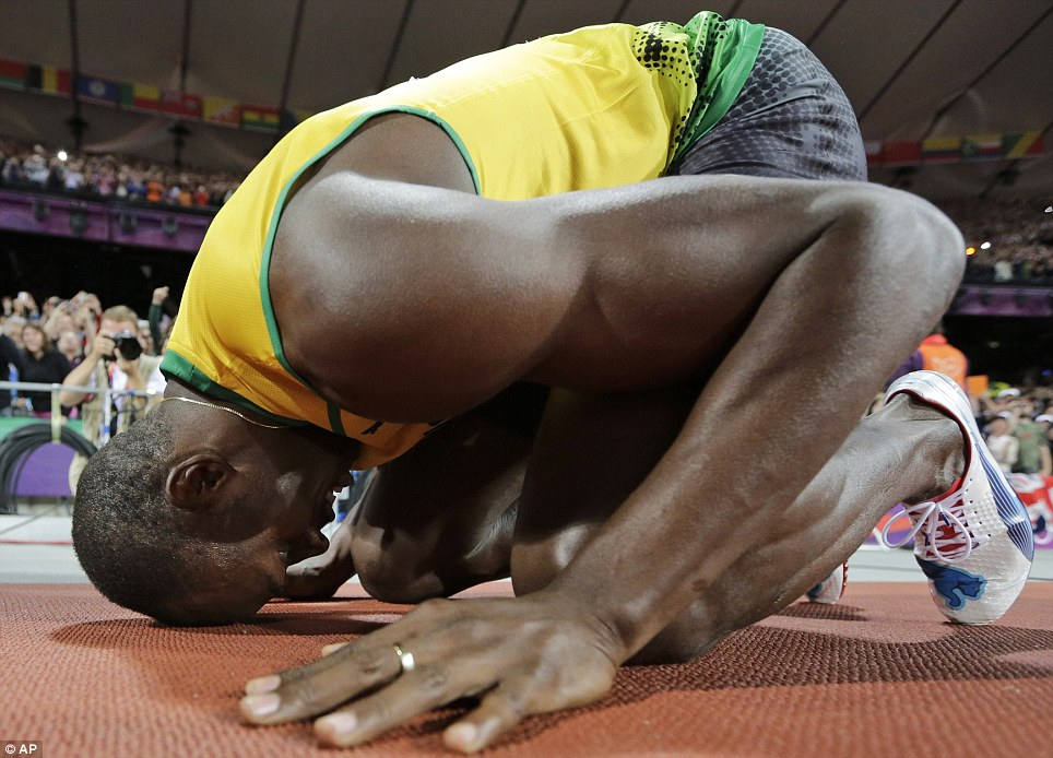 Taking a bow: Jamaica's Usain Bolt kneels and rests his head against the track in the Olympic Stadium after recording the second-fastest time ever