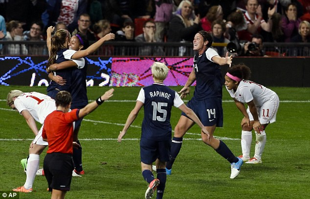 Celebration time: Alex Morgan is hugged by team-mates after nodding a dramatic winner
