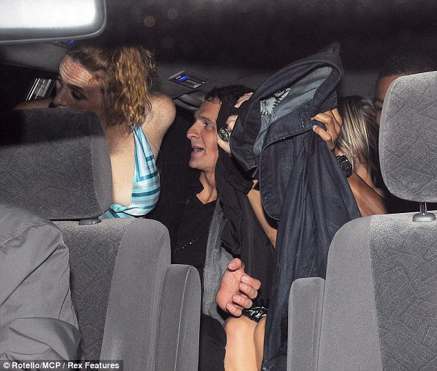 Tight squeeze: One female tries to conceal her face as her friend piles into the cab and sits on top of Lochte's lap