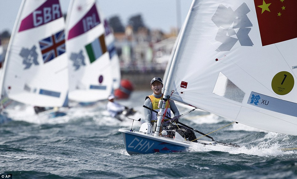 Xu Lijia of China celebrates her gold medal as she crosses the finish line during the Laser radial sailing medal race
