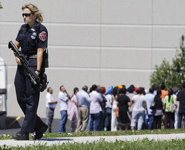 Tragedy: Police watch over the Sikh temple, where a white supremacist shot dead six people on Sunday. A police officer, Lt. Brian Murphy, was shot multiple times as he responded to the scene