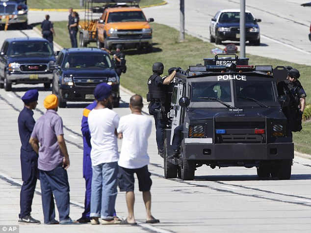 Fears: People watch police personnel outside the Sikh Temple in Oak Creek after the shooting