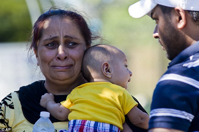 Heartbreak: A woman struggles to contain her tears after the shooting spree on Sunday at the temple