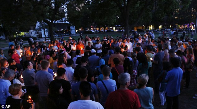 Vigil: Mourners take part in a candle light vigil for the victims on Sunday night
