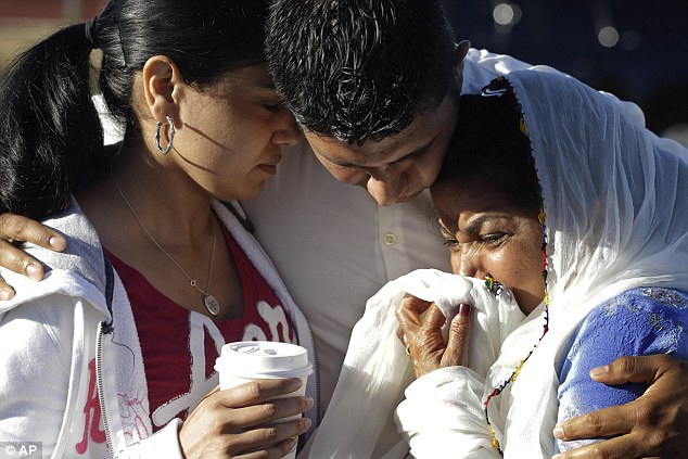 Struggle: Amardeep Kaleka, son of the president of the Sikh Temple of Wisconsin comforts members of the temple. His father Satwant Kaleka, 65, died in the shooting with four other priests