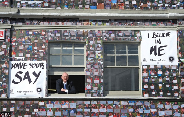 'Don't judge youngsters': Trevor Reeve, the owner of the fire-destroyed House of Reeves, looks through the window of his other store, which has been covered in 4,000 images of young people holding positive statements