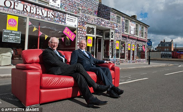 Lookig forward: House of Reeves owners Maurice Reeves (left) and his son Trevor pose for pictures outside the furniture store after unveiling their messages of hope on the one-year anniversary of the riots