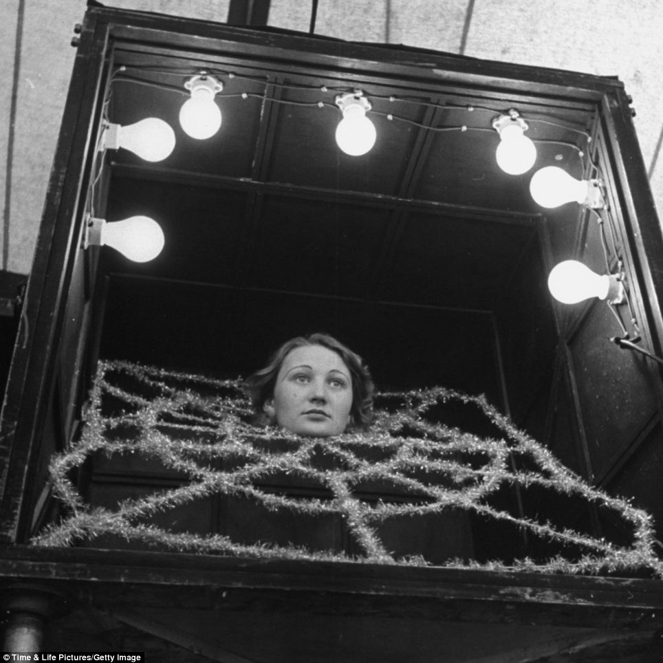 Out of her mind: A girl performs as a headless woman. Only her head can be seen in a spider web made of tinseled garlands
