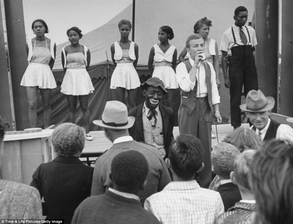 Making a mockery: Five African-American girls from the Harlem Dandys wait on stage as a barker announces their minstrel show and its main star
