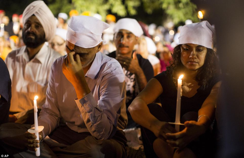 People cover their heads as they pay tribute to the victims of a mass shooting at the Sikh temple