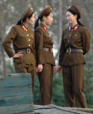 Female soldiers chat on the bank of the Yalu River in the North Korean town of Sinuiju