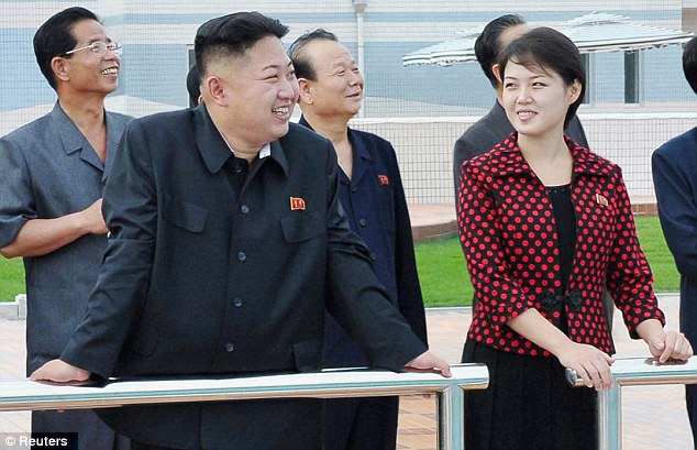 Contrast: North Korea's first lady brought some colour to proceedings when she visited the Rungna People's Pleasure Ground with leader Kim Jong-Un (left)