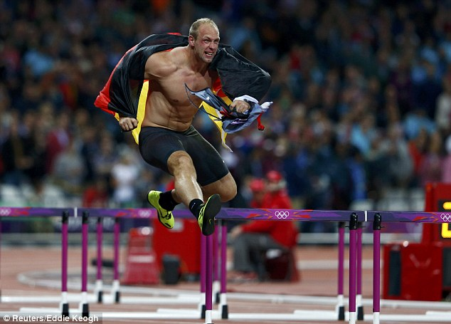 Jumping for joy: After ripping his shirt off, Harting continued his victory lap by vaulting the hurdles which had been placed for the women's 110m final